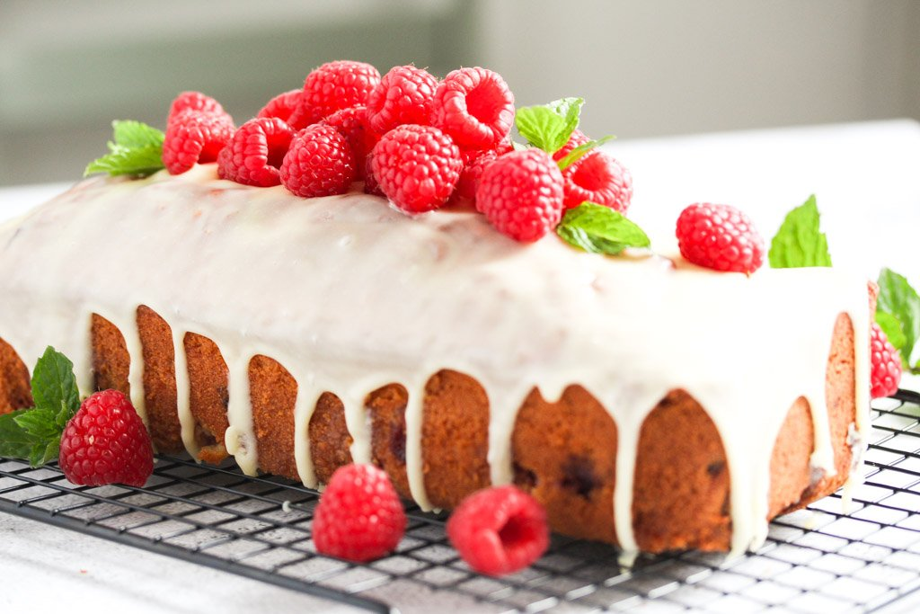 white chocolate drizzling down the sides of a cake with berrries.