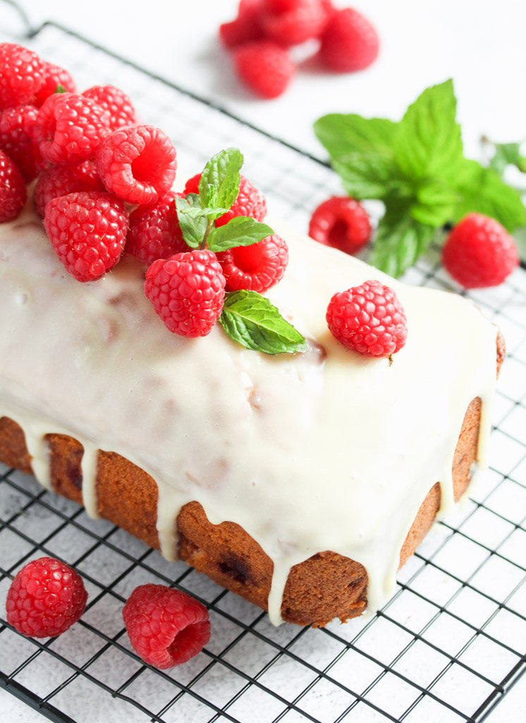 raspberry white chocolate loaf cake resting on a wire rack.
