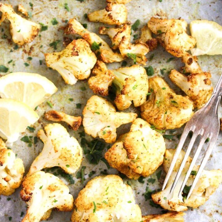 close up roasted frozen cauliflower, a vintage fork and lemon slices.