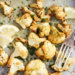 baked cauliflower on a tray with a fork and lemon slices.