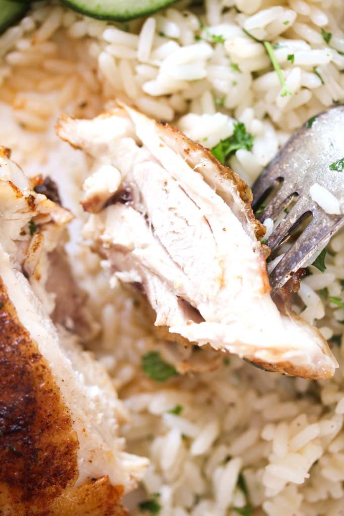 cut white piece of poultry held by a fork close up.