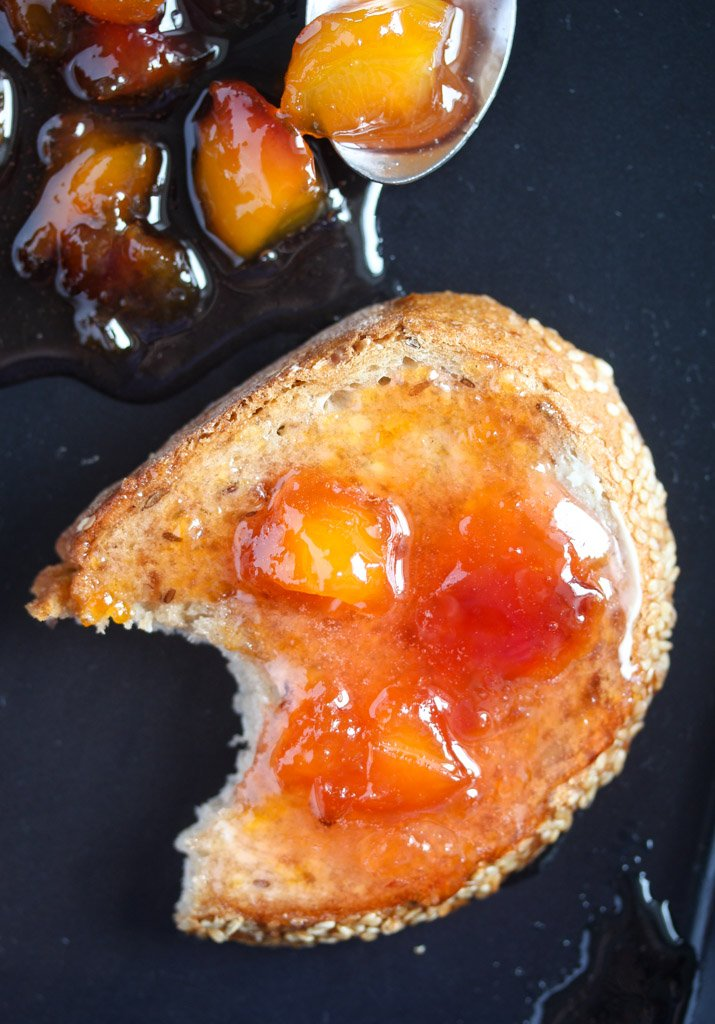slice of bread with peach jam and some spilled jam beside it.