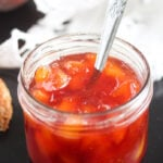 jam preserves without pectin in a small jar on a black board with a white cloth behind.