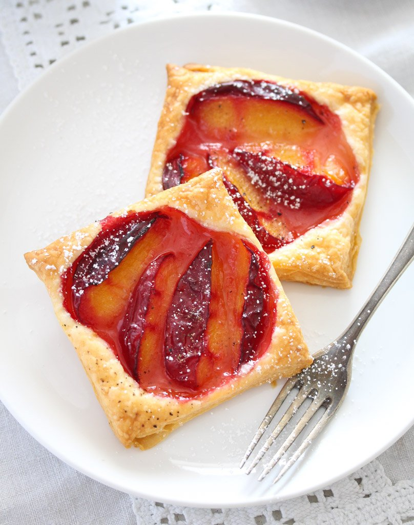 two pastry tartlets with fruit on a white plate with a vintage fork.
