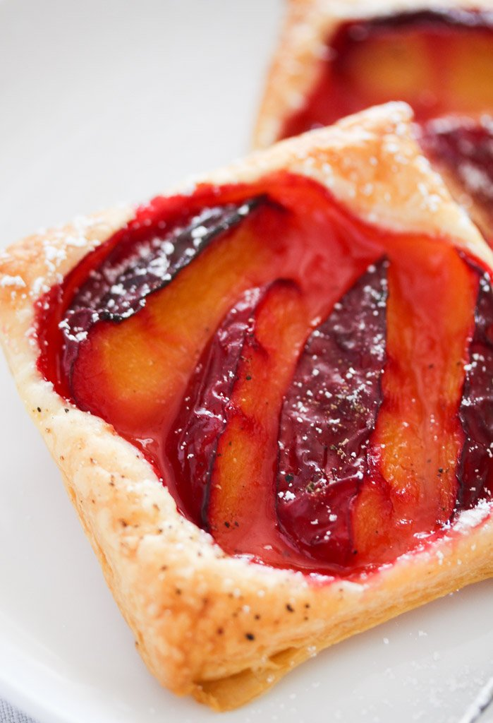 close up of one shiny red plum tartlet.