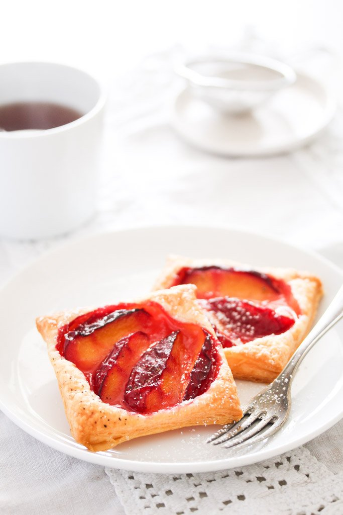 two puff pastry plum tarts on a white plate with a cup of coffee behind.