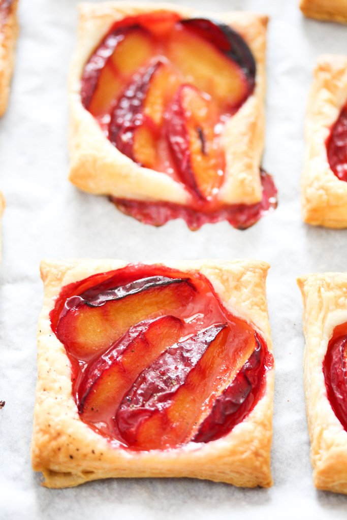 two plum pastries on white parchment paper.