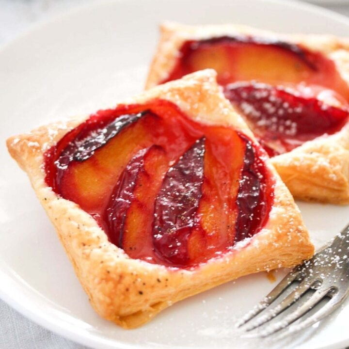 puff pastry plum tarts on a plate close up.