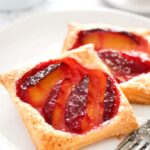 pinterest image of two plum pies on a plate.