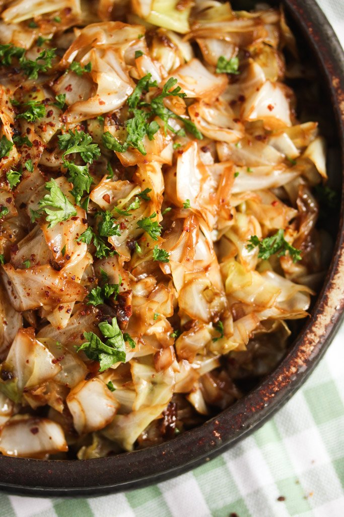 close up of fried pointed cabbage in a brown rustic bowl.